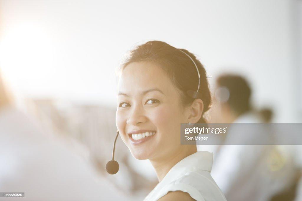 Donna d'affari con auricolare in ufficio : Foto stock