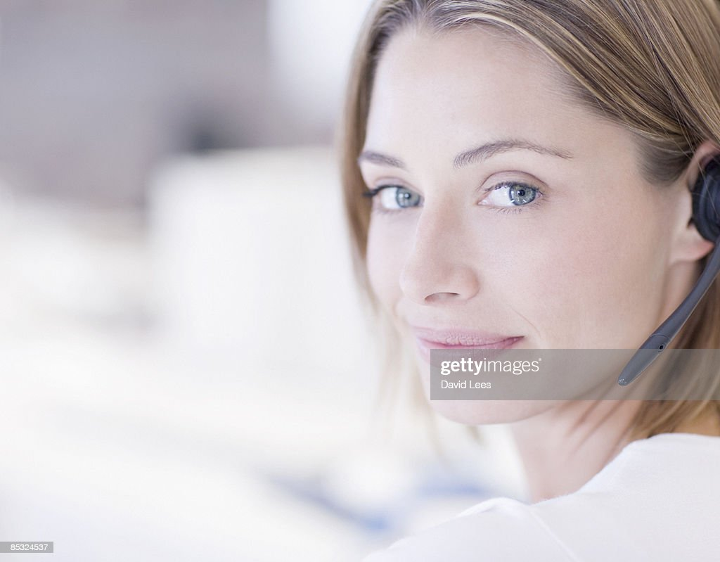 Businesswoman wearing headset, smiling, close up : Stock Photo