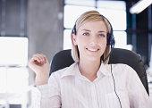Businesswoman wearing headset, smiling