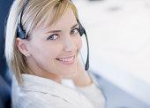Businesswoman wearing headset, smiling, portrait