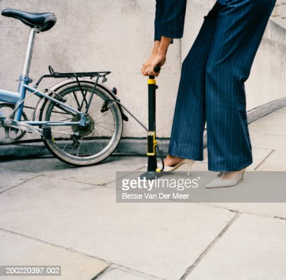 Businesswoman wearing high heeled shoes pumping bicycle tyre