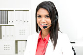 Businesswoman wearing microphone headset - operator, call center, telemarketing and customer service staff concepts