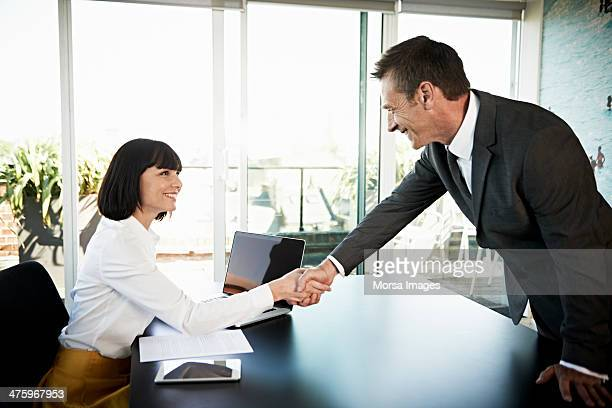 Businesswoman welcoming man to meeting