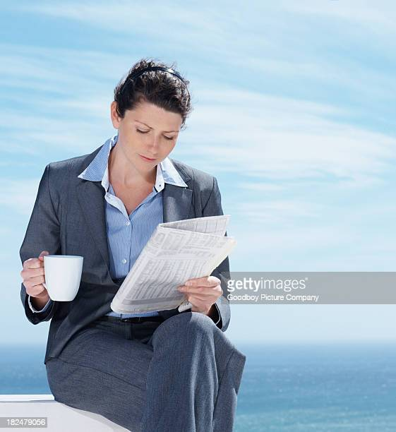 Businesswoman with a coffee and reading newspaper by sea