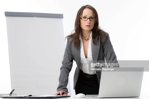 Businesswoman with a laptop and a flipchart