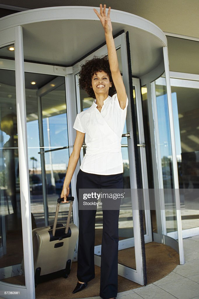 Businesswoman with a suitcase hailing a taxi : Stock Photo