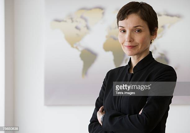 Businesswoman with arms crossed in front of map