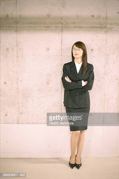 Businesswoman with arms crossed leaning by wall