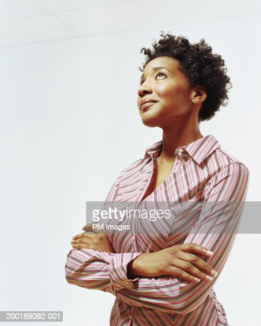 Businesswoman with arms folded looking upward, smiling : Stock Photo