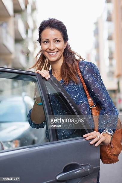 Businesswoman with bag standing by open car door on street