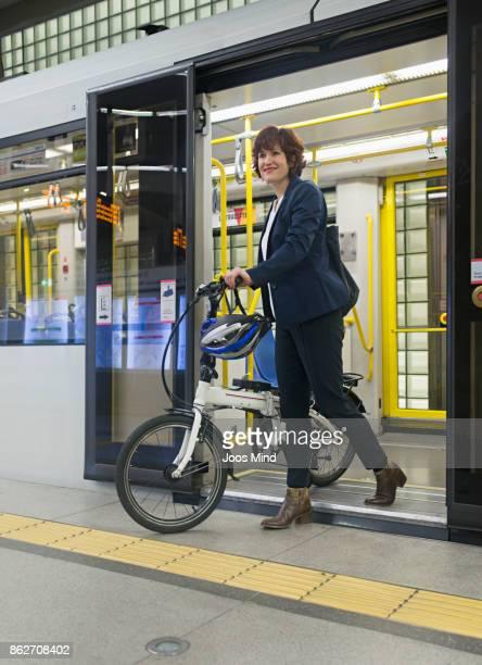 businesswoman with bike leaving subway train