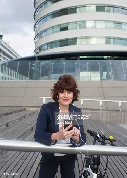 businesswoman with bike, using headset and smart phone