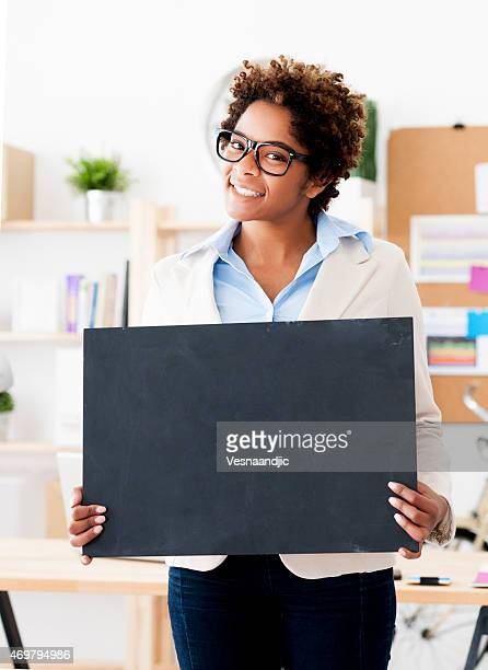 Businesswoman with blank sign at office