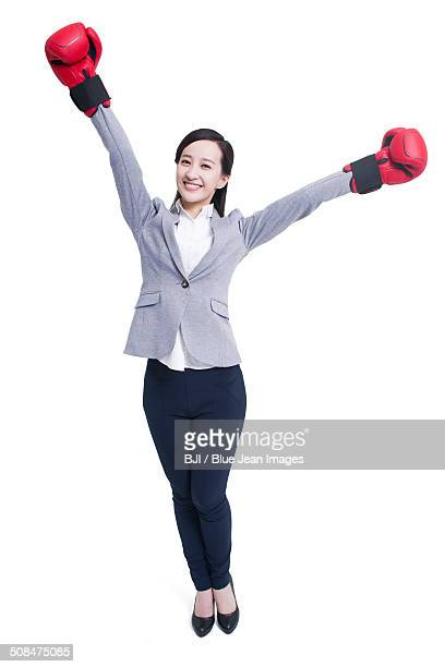 Businesswoman with boxing gloves celebrating victory