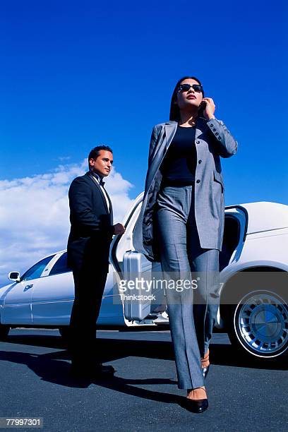 Businesswoman with cell phone exiting limousine