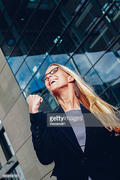 Businesswoman with clenched fist outside office building