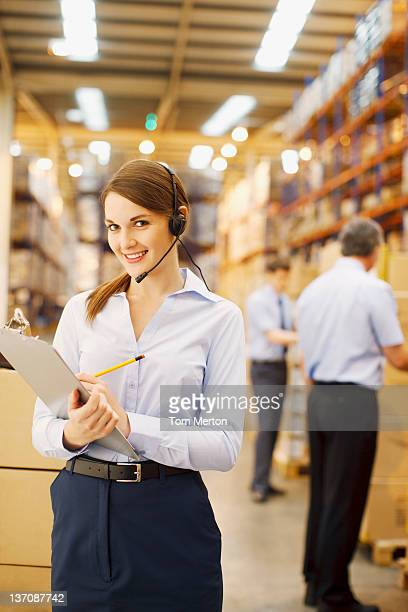 Geschäftsfrau mit Zwischenablage im warehouse Arbeiten