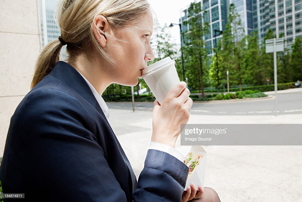 Businesswoman with coffee and sandwiches : Stock Photo