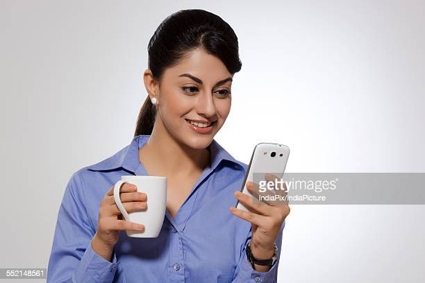 Businesswoman with coffee mug reading text message on smart phone against gray background