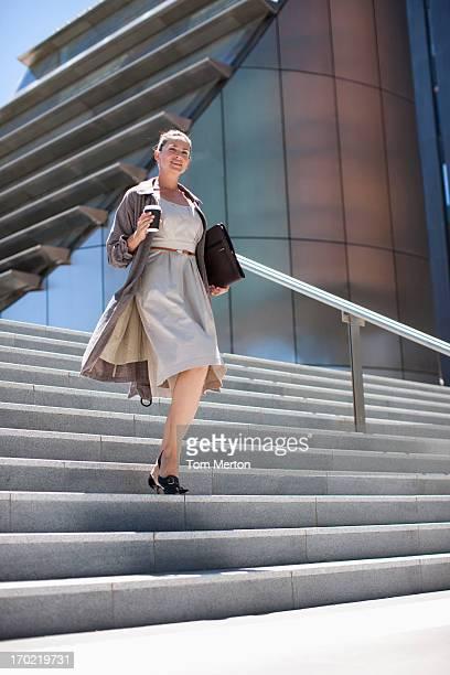 Femme d'affaires avec une marche le long de quelques marches en plein air