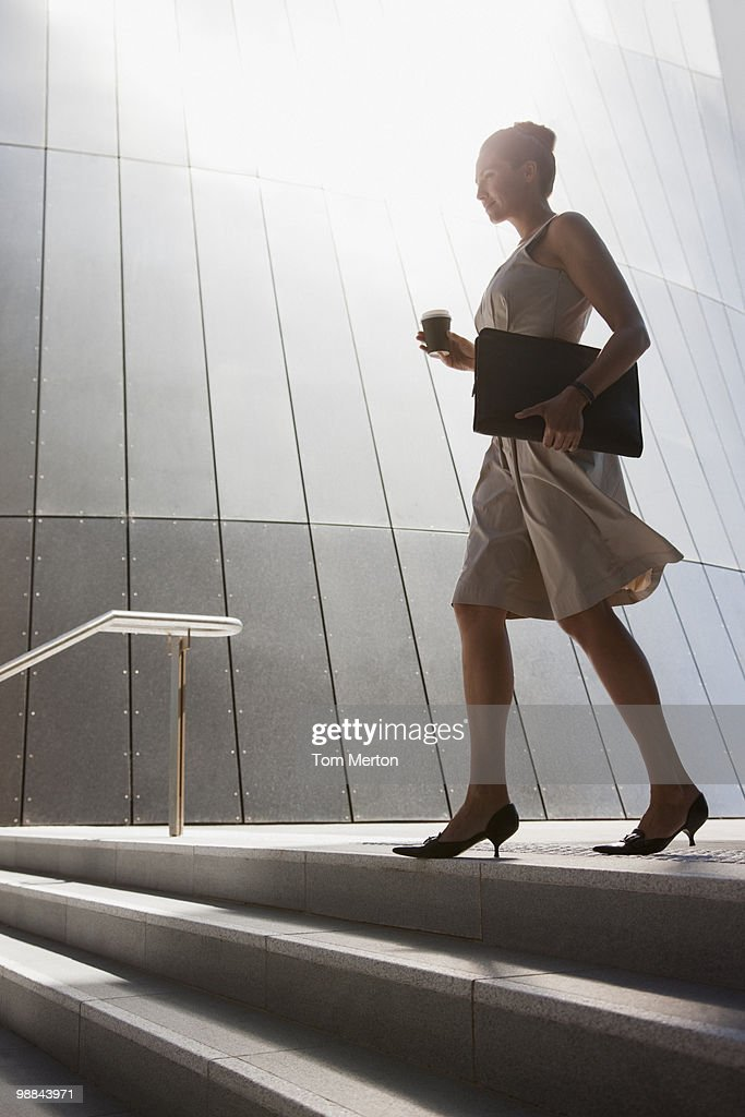 Businesswoman with coffee walking down steps outdoors : Stock Photo