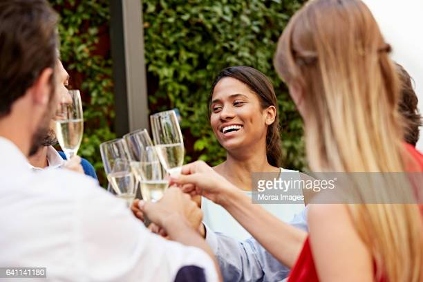 Businesswoman with colleagues toasting champagne