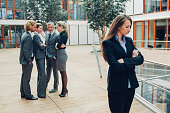 Businesswoman with crossed arms, excluded from group of business people
