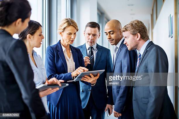 Businesswoman with digital tablet and team of associates