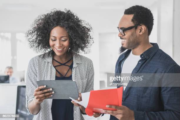 Businesswoman with digital tablet smiling and talking to man with red file