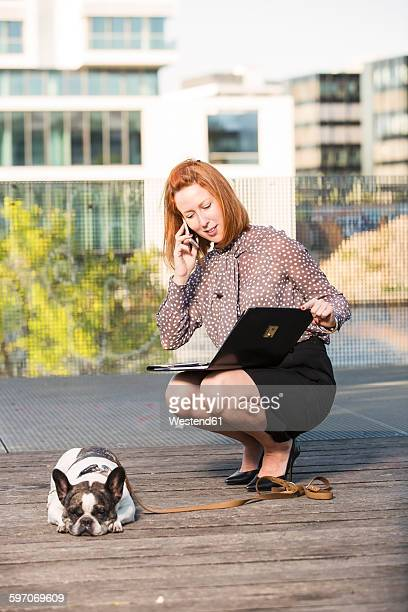 Businesswoman with dog telephoning on roof terrace