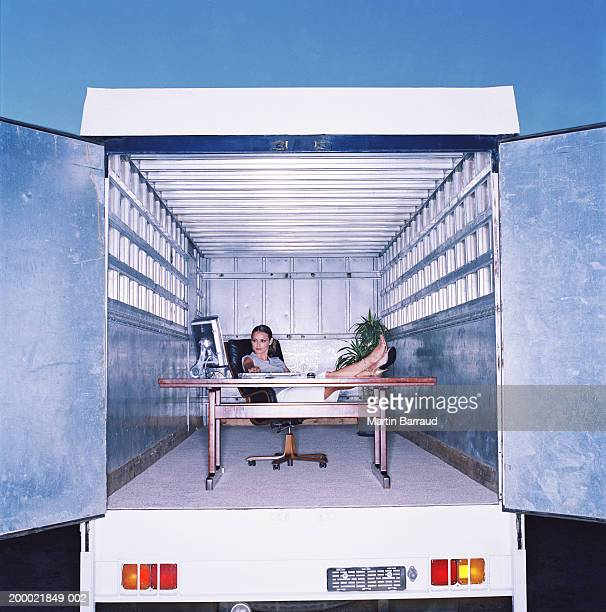 Businesswoman with feet on desk in back of lorry