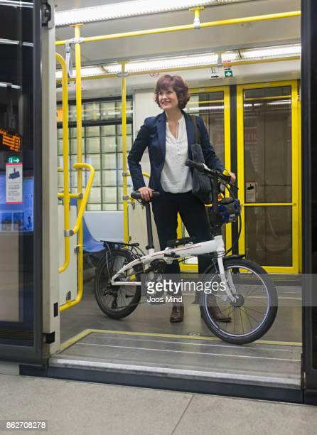 businesswoman with folding bike in subway train