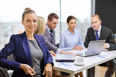 business, technology and people concept - smiling businesswoman with eyeglasses in office with team on back