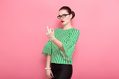 Portrait of attractive cheerful businesswoman with hair bun in striped blouse and eyeglasses showing fuck gesture sign isolated on pink background with copyspace.