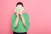 Portrait of businesswoman with hair bun in striped blouse and eyeglasses covering her face with fan of euro bills isolated on pink background with copyspace winning in lottery money withdraw concept.