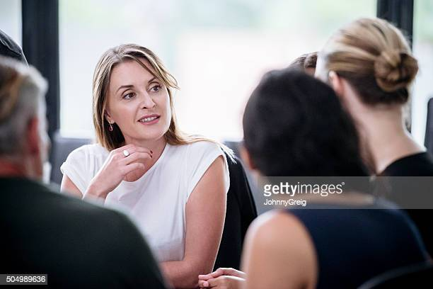 Businesswoman with hand on chin listening to colleague in meeting