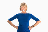 Portrait of happy mature businesswoman with hands on hip standing over white background