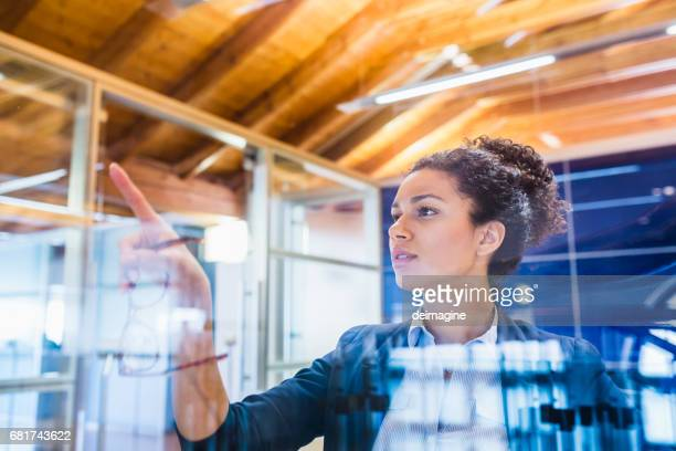 Businesswoman with index finger on window panel