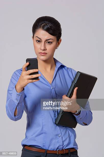 Businesswoman with laptop reading text message on smart phone against gray background
