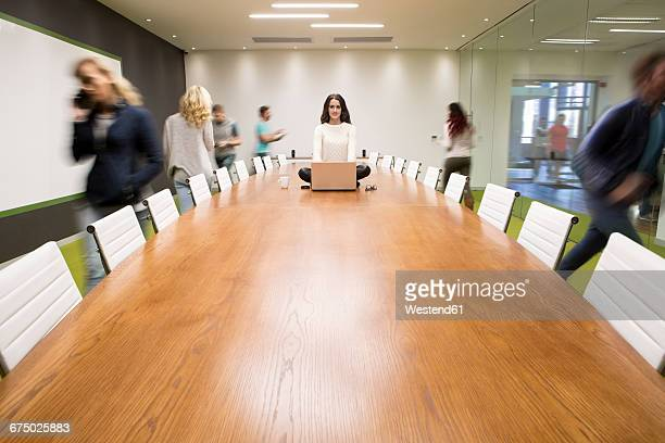 Businesswoman with laptop sitting on conference table with people running around