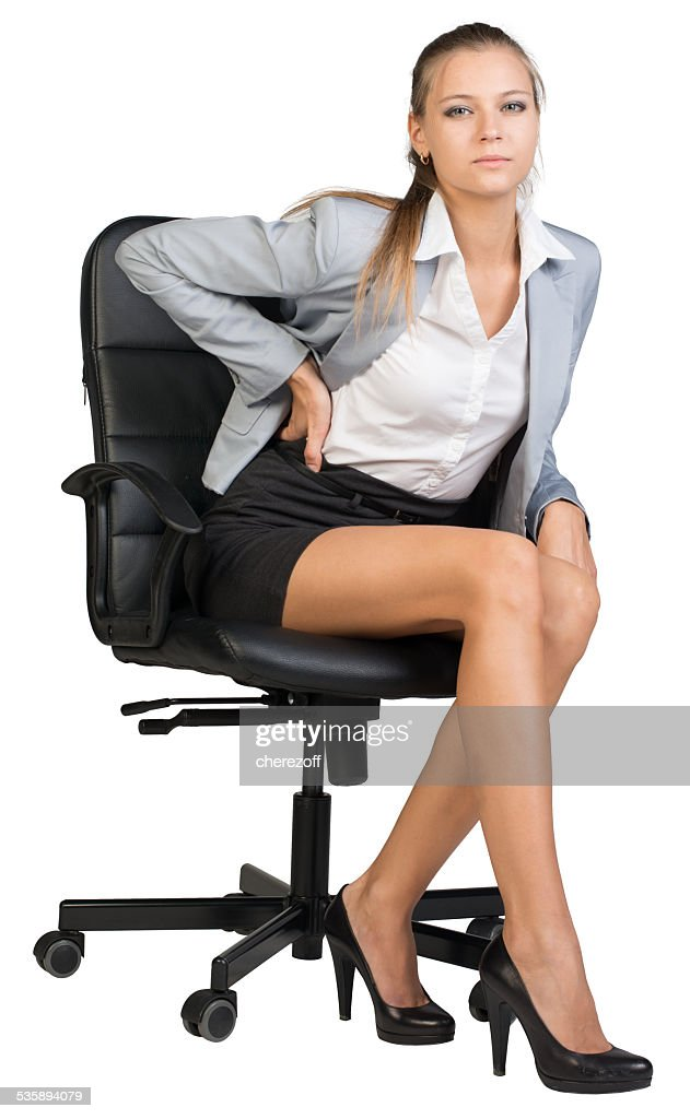Businesswoman with lower back pain from sitting on office chair : Stockfoto