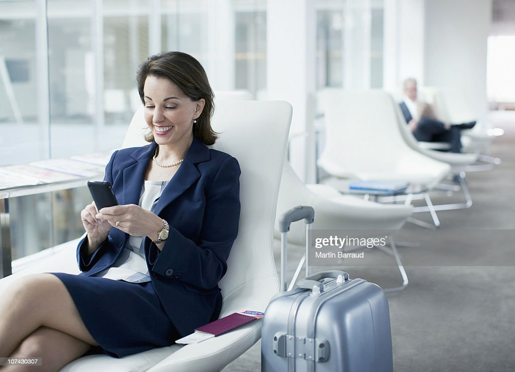 Businesswoman with luggage sitting in airport waiting area : Stock Photo