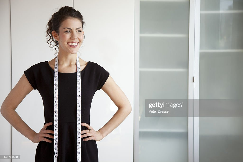 Businesswoman with measuring tape around her neck : Stock Photo