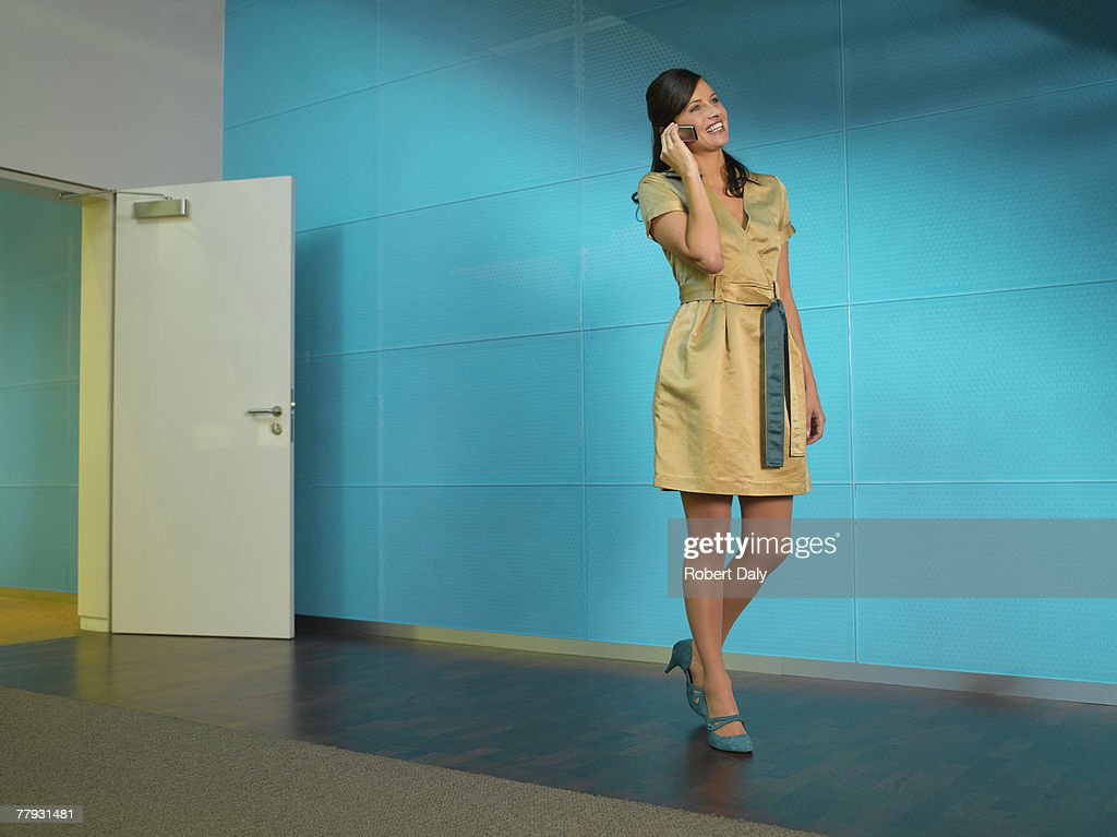 Businesswoman with mobile phone in blue office smiling : Stock Photo