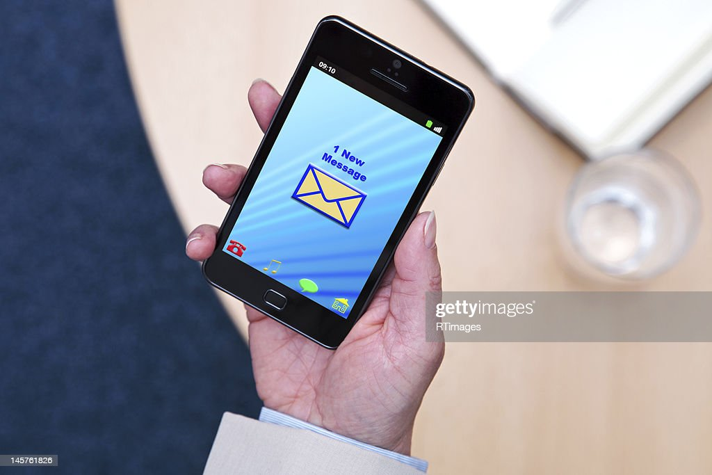 Businesswoman with new message on her phone : Stock Photo