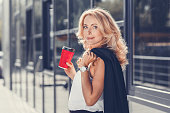 beautiful blonde businesswoman holding disposable coffee cup and looking at camera