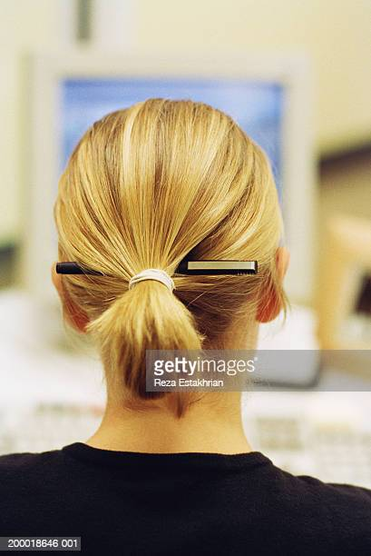 Businesswoman with pen in hair, rear view, close-up