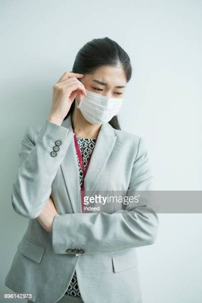 Businesswoman with protective mask, touching temple