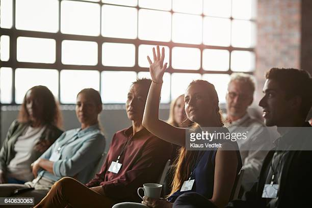Businesswoman with raised hand at convention