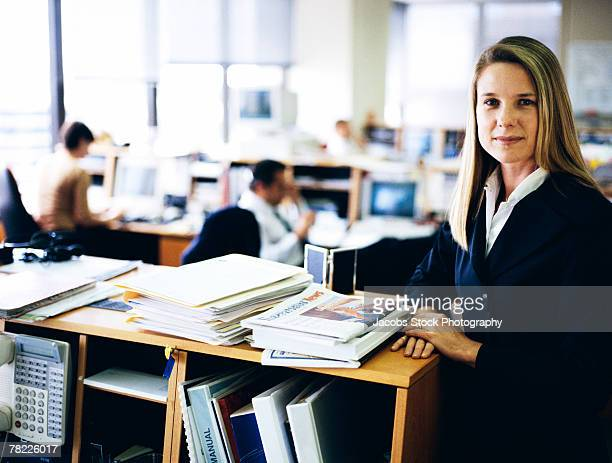 Businesswoman with shelves of paperwork